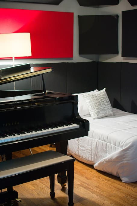 Tracking room with grand piano and fold-out futon with comfortable twin sized mattress topper.