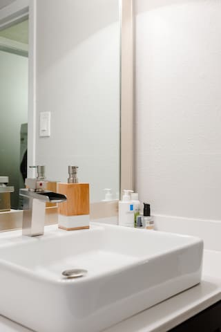 Modern vanity space in shared bathroom.