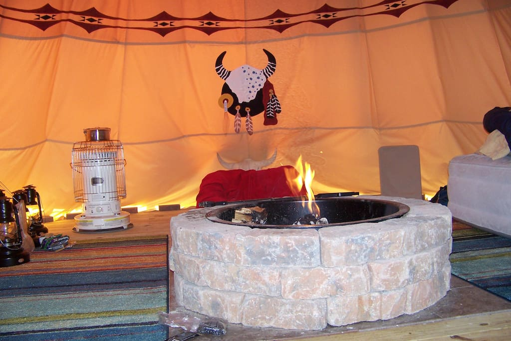 Inside view or the tipi with the firepit and fire.  All cooking is done over the fire or outside on your choice of camp stove.