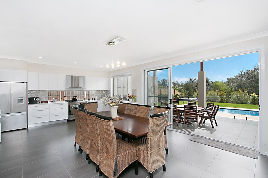 Dining and kitchen area with access to outdoor alfresco area and pool