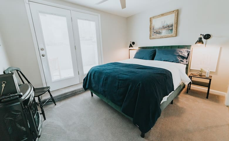 The charming Queen bedroom with its own electric fire place and access to an outdoor patio.