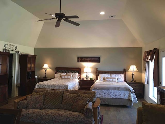 """Spacious room with beautiful view and opening to a private covered deck  with Two comfortable queen beds and a sleeper sofa, an ambient """"fireplace"""" and a second comfy sofa. Large walk in closet."""