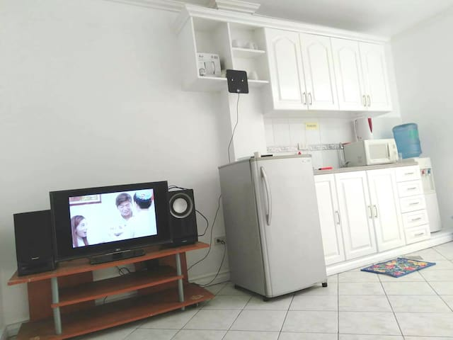 """32"""" LED HD TV, Refrigerator, Microwave oven,  cupboard with sink & utensils, and water dispenser."""