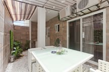 The spacious and romantic back patio with plants & a large table for evening relaxing moments.