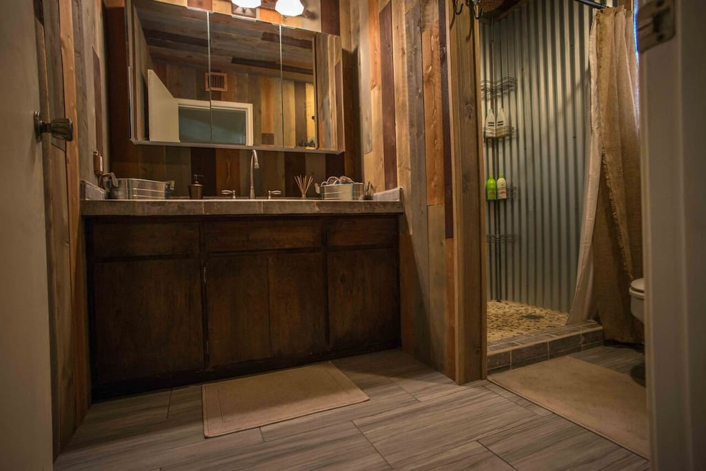 Beautifully remodeled rustic themed bathroom. Unique steel and exposed copper shower with a pebble stone floor, incorporating the elements of metal, wood, stone, and water. Complimentary organic and eco-friendly shampoo, conditioner, and bodywash. Shared with one other room.