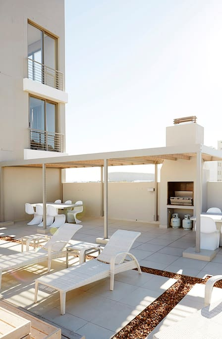 Rooftop BBQ area with sun-chairs and pool deck