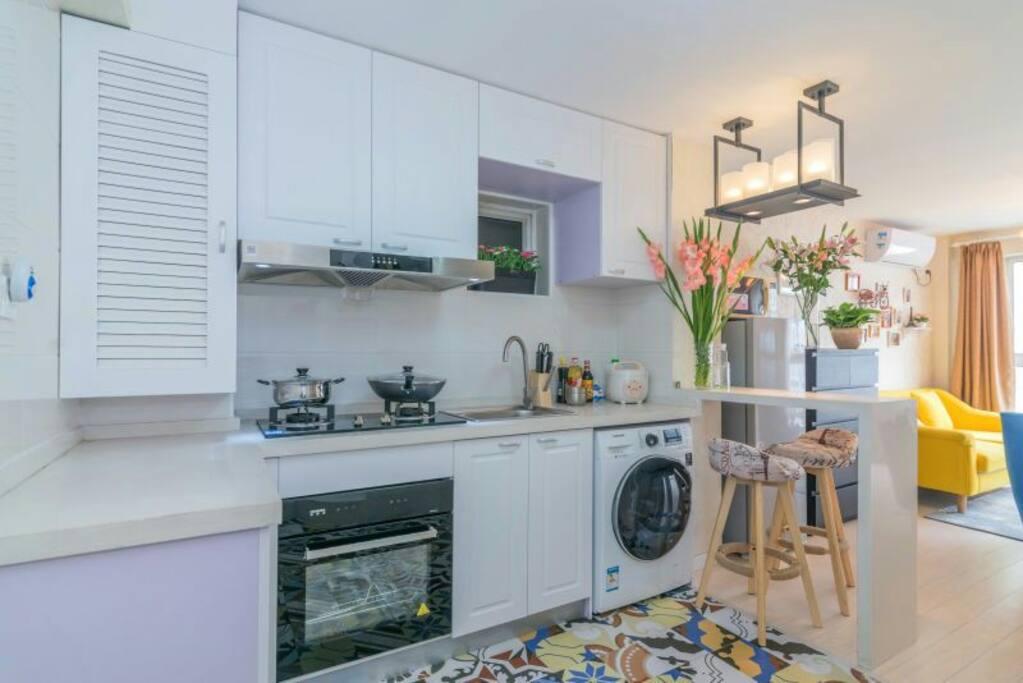 开放式厨房,旁边是个客厅,带个小吧台,非常喜欢这个设计,洗衣机也是带烘干的,三星的,品牌。