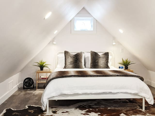 Our cozy bedroom is tucked under the low peaked ceiling. A plush Queen sized bed features bedside reading lights, alarm clock, portable Bluetooth speaker and an additional fan.