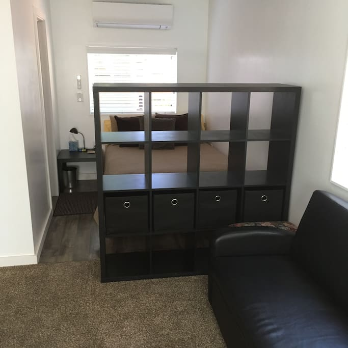 Bedroom area behind shelf unit
