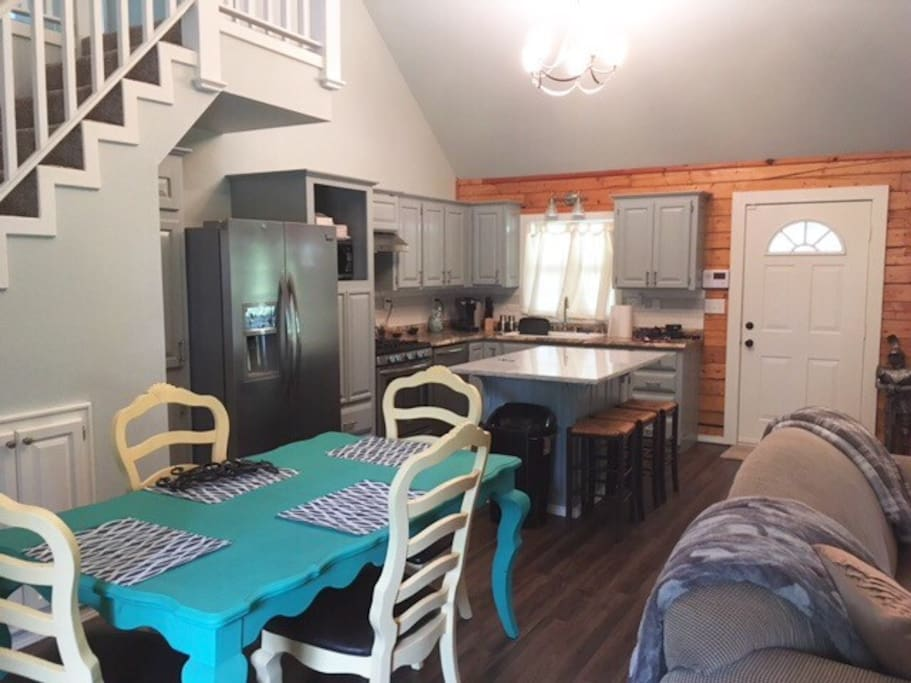 Fully equipped kitchen with microwave, gas stove, dining area.