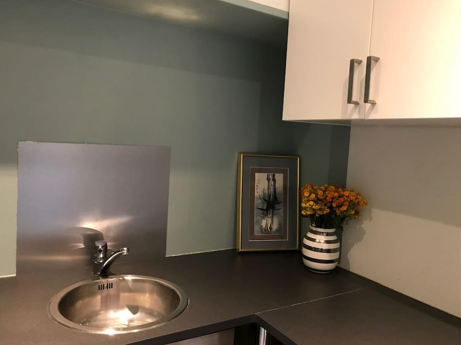 Kjøkken med oppvaskmaskin, kjøleskap/frys og komfyr.