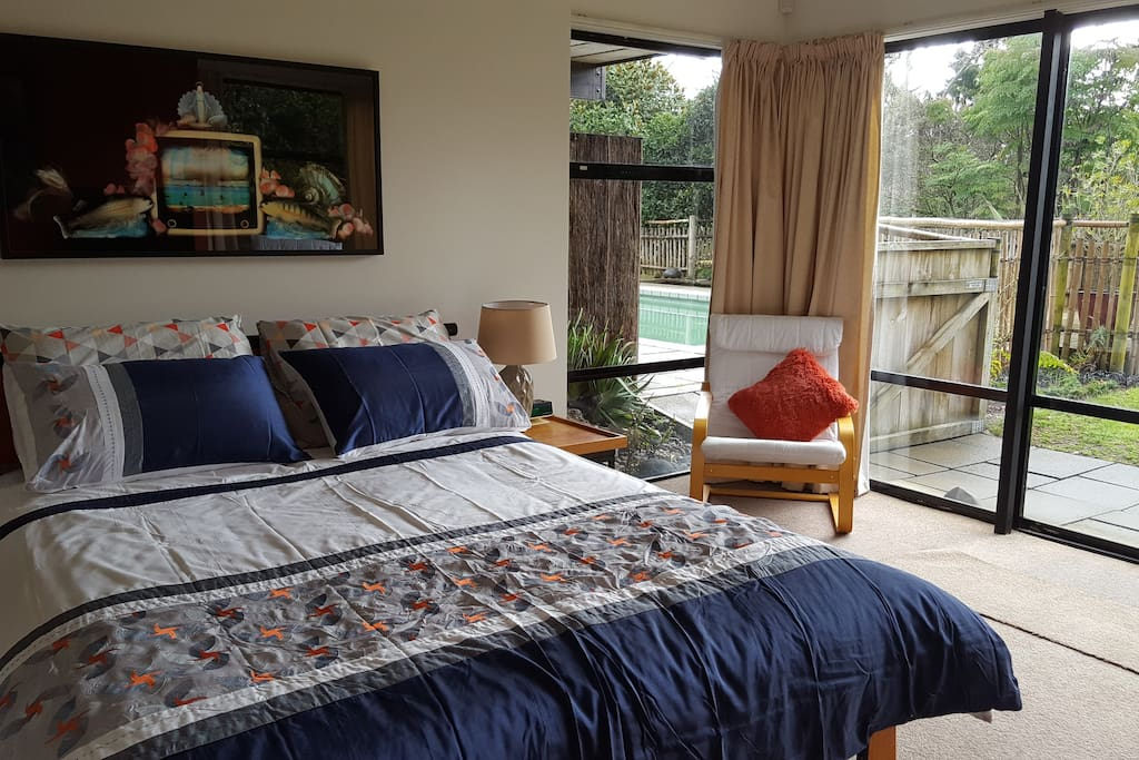 Queen sized bed looking out to the Whanganui River. Private patio area and access to swimming pool.