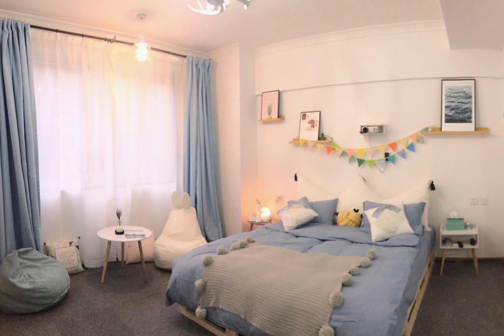 房间的卧室区域是一张舒适的双人大床,有柔软的亲肤棉床品,每客一换,铺设了地毯,还配备了懒人豆豆沙发可以休息看书放空自己。