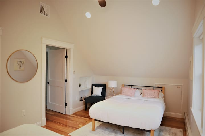Two full size beds in a large bedroom (#2) with a nice garden view and plenty of natural light.