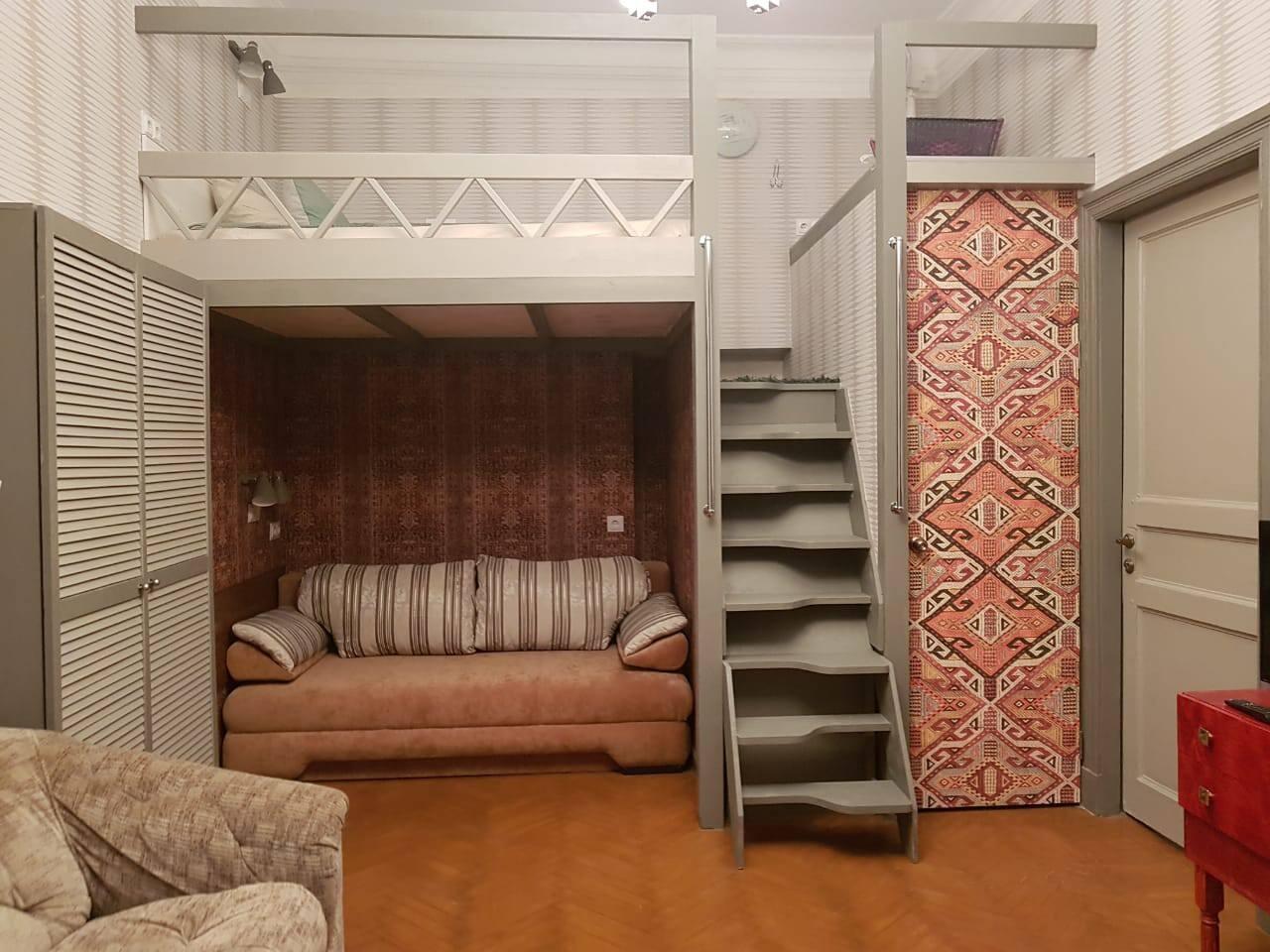 Гостиная с двуспальным диваном внизу и двойным спальным местом на антресолях