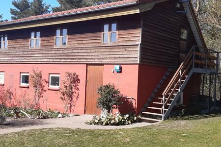 Vestbirk hus med udsigt over eng og marker.