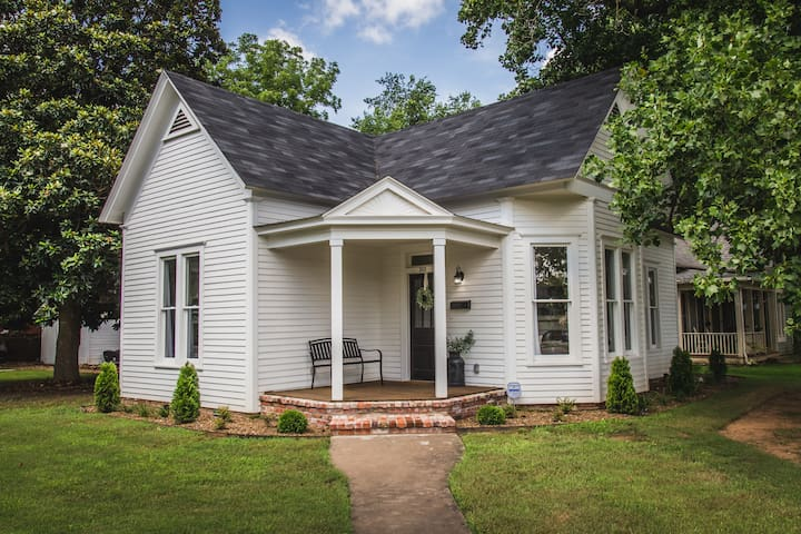 The cottage is situated on a corner lot and has a front porch.