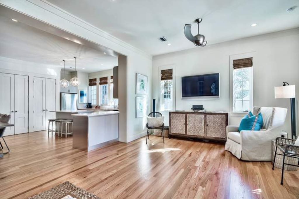 The great room has hardwood flooring, recessed lighting, and access to the covered back patio