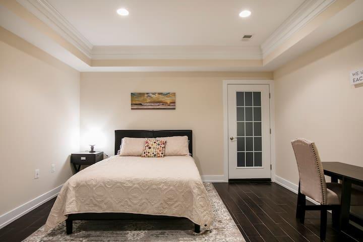 Bedroom #1 overview of queen size bed, nightstand, desk and patio door