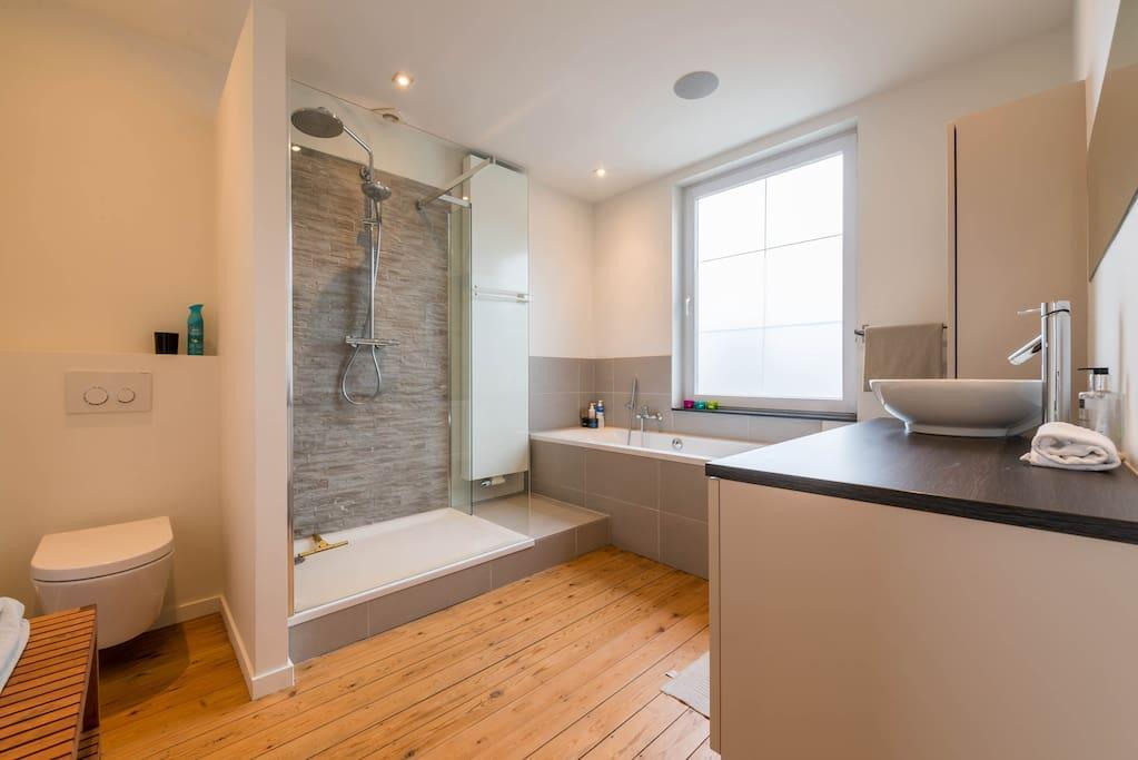 ruime badkamer met ligbad en douche