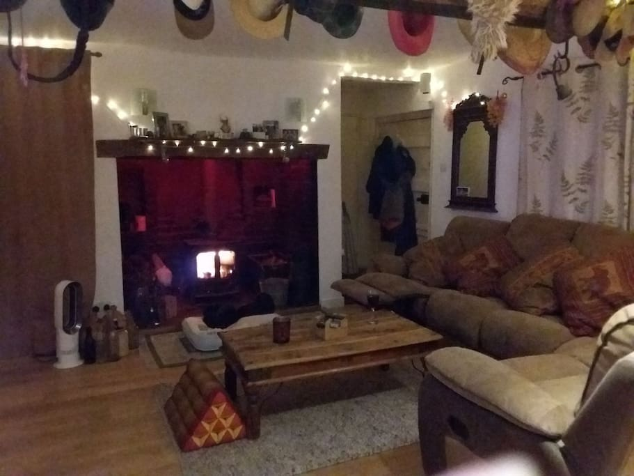 Living Room with Gorgeous Inglenook Fireplace and log Wood Burner. Reclining Chairs and Comfy sofa perfect for entertaining.