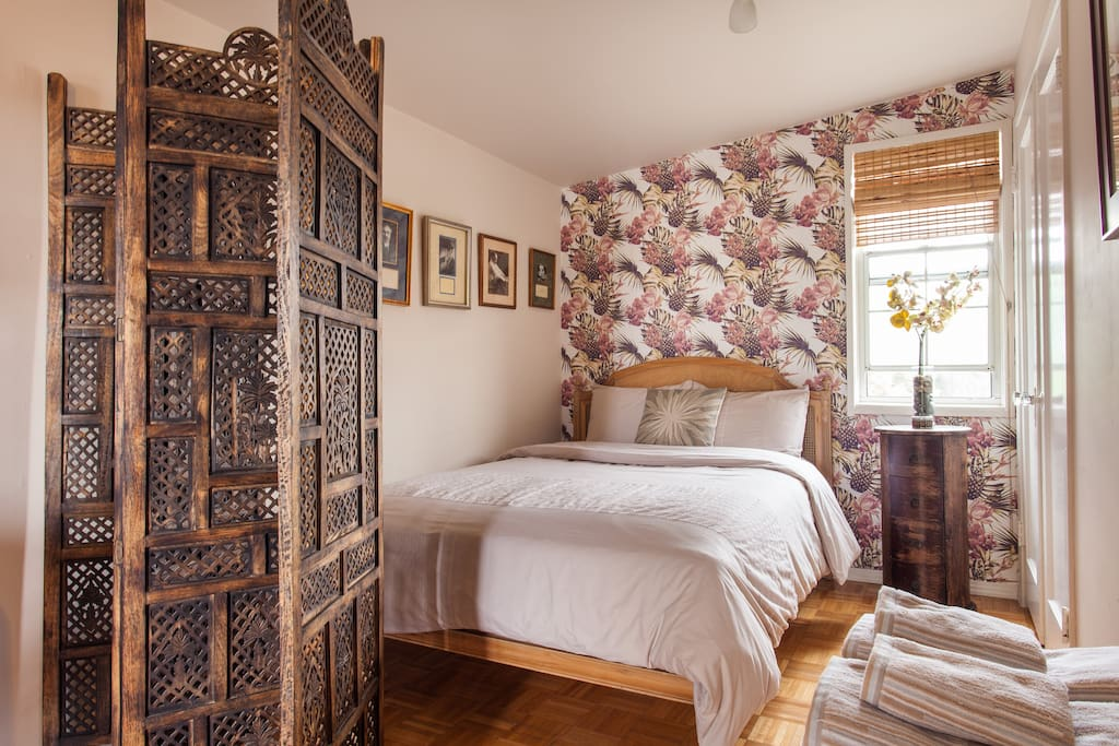 Bedroom includes a double bed, luxury mattress, and privacy screen.