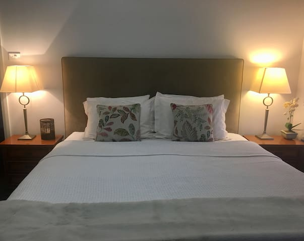 King Bed with beautiful linens and candles