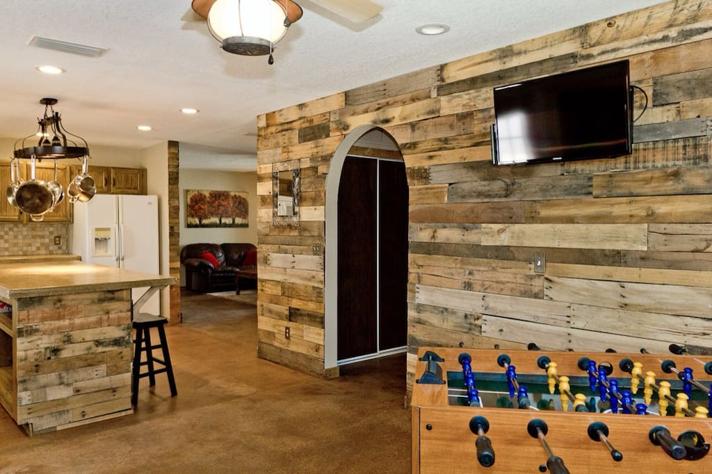 Pallet wood walls with a large island in the kitchen and a foosball table and flat screen tv