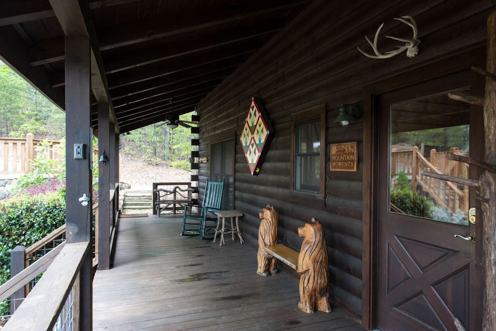 The covered front porch has a rocking chair and unique bench.