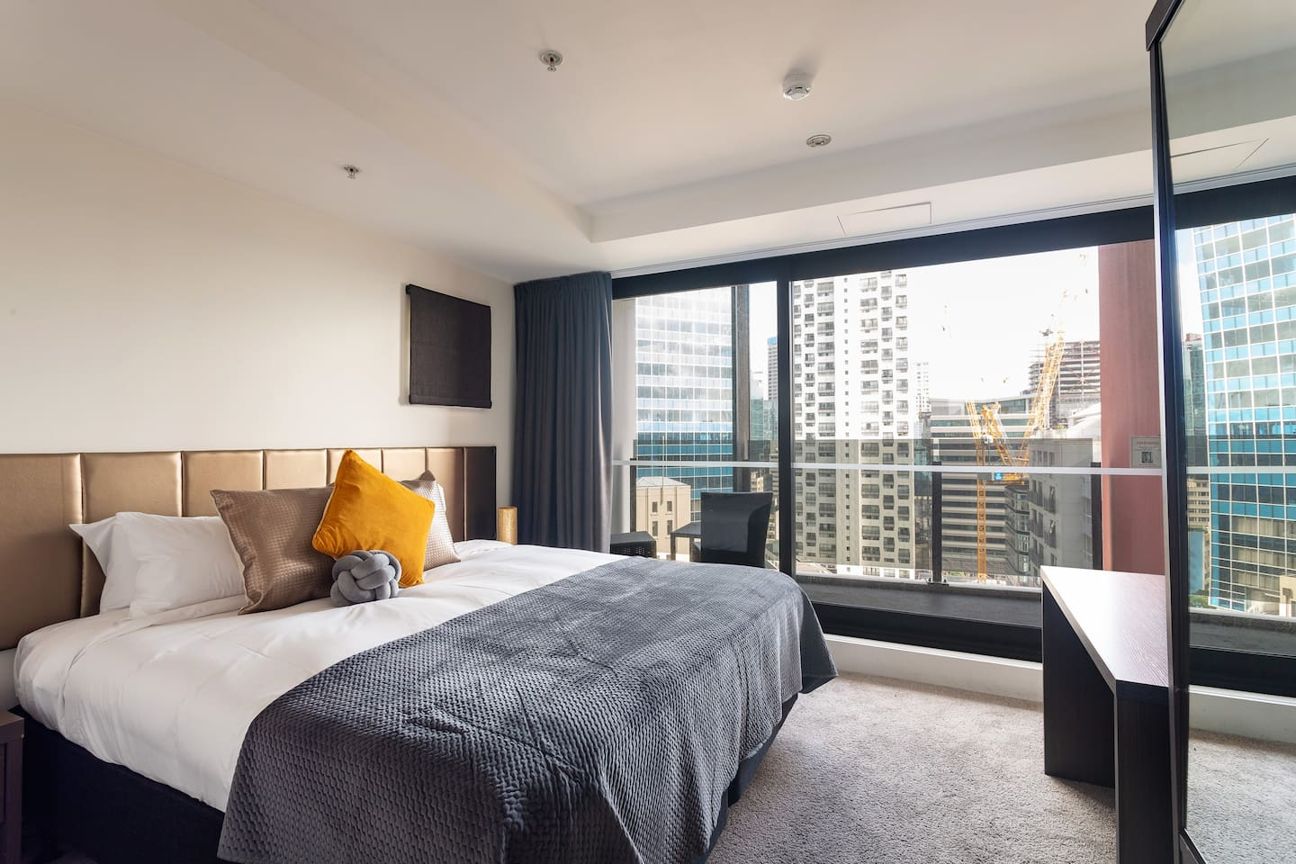 Master bedroom with view out to city from balcony