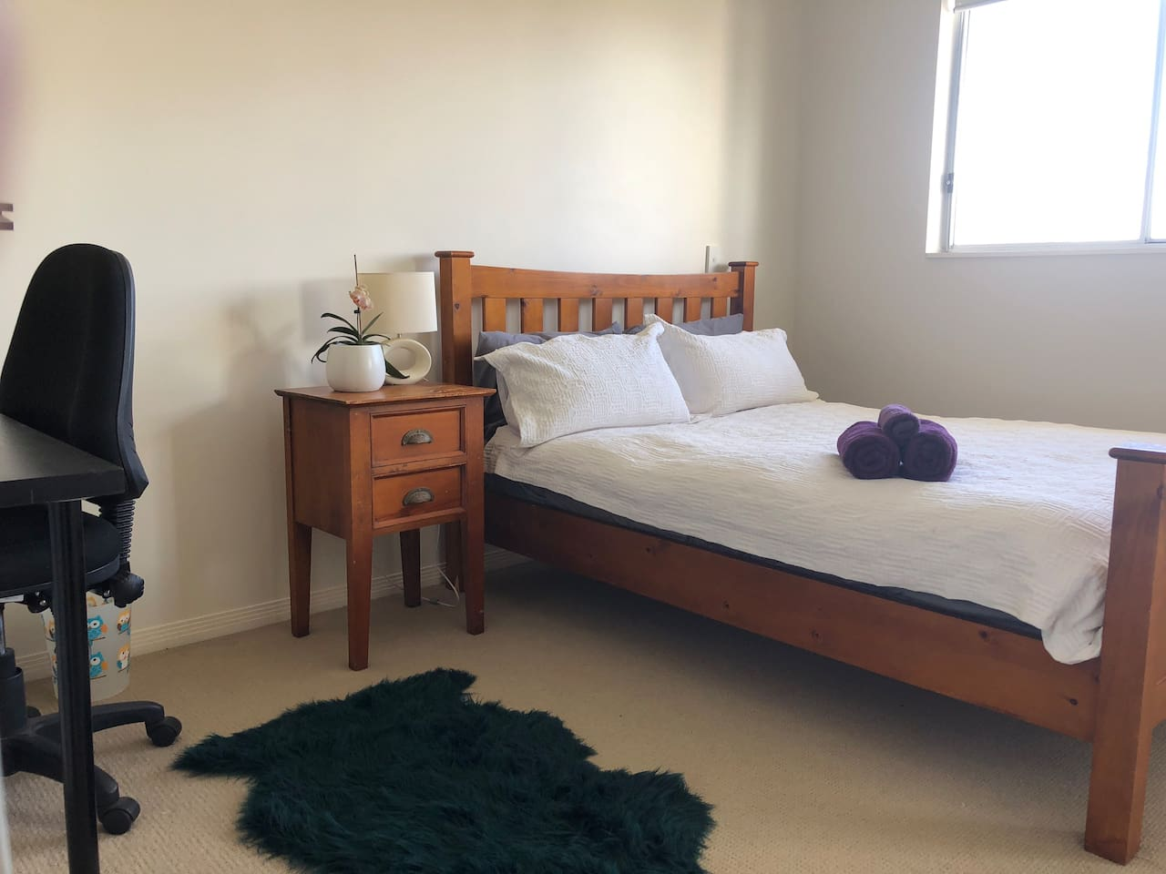 Double sized room with double bed, double wardrobe, shelf, drawers and desk and chair.