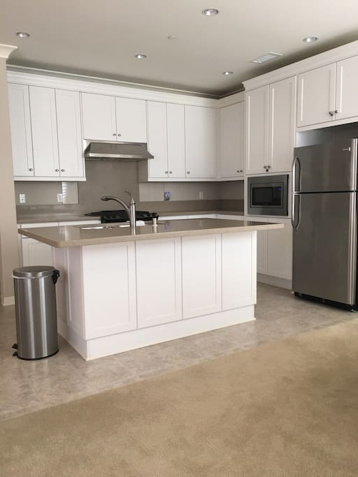 Open concept kitchen area with new appliances