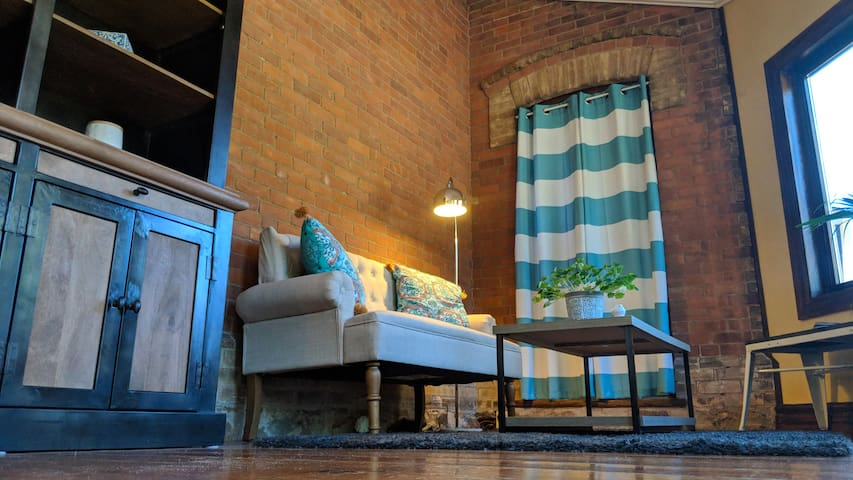 Lots of charm as the brick wall serves as the backdrop for your living room