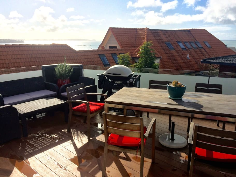 Large first floor deck, with ocean views, BBQ, dining table and sofa area.