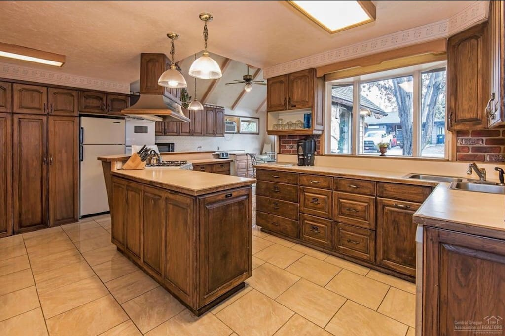Large kitchen equipped with 3 ovens, 2 refrigerators and lays of large pans for groups