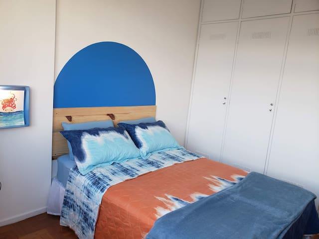 Confortável cama de casal com roupa de cama completa.
