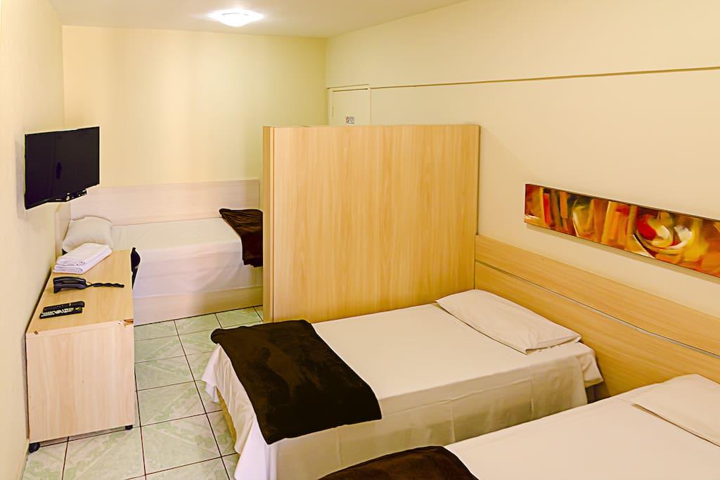 O Villa Neves possui 25 suítes. Por isso, há vários quartos com três camas de solteiro. Eles são escolhidos de acordo com a disponibilidade no dia da reserva. Este quarto tem três camas de solteiro, uma estante, mesa com cadeira, TV 28 polegadas.