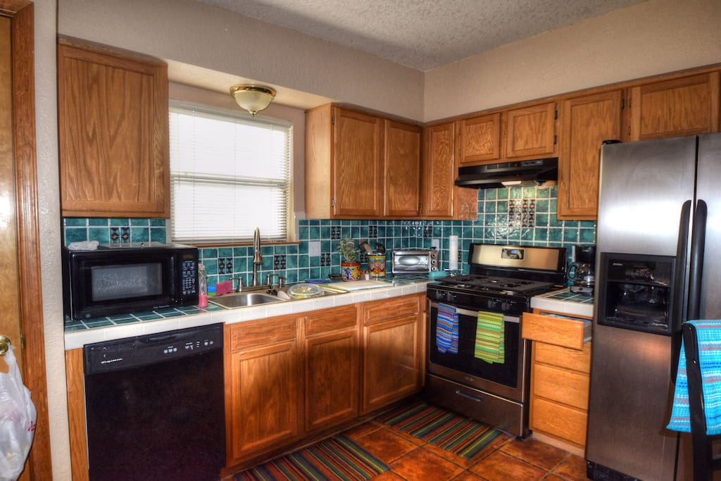 Kitchen with side by side fridge, dishwasher, microwave and seating for four.