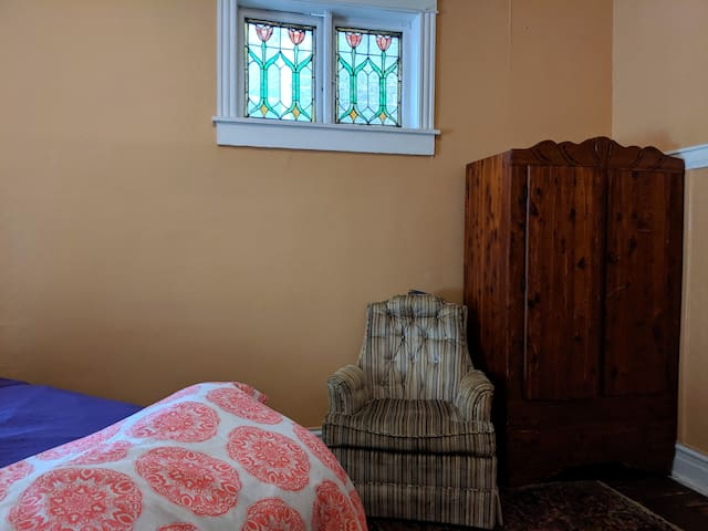 Stained glass windows, armoire to stash your things in,  11' ceilings.