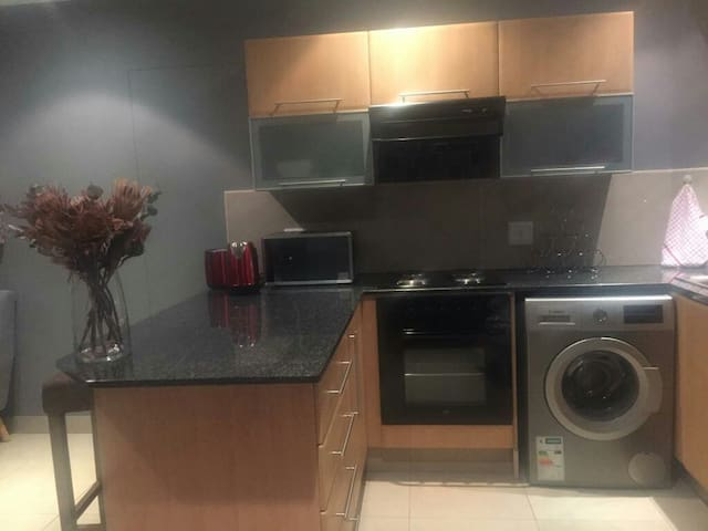 Kitchen with the following appliances :  washing machine,  laundry dryer, kettle, pots, Refrigerator,microwave oven, toaster etc