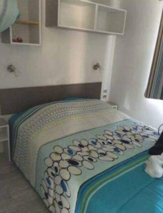 Chambre 1 avec un lit double,une armoire,une étagère au dessus du lit et des tables de chevet