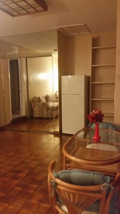 Closet with mirror sliding doors.  Lots of shelving on the right, fridge, microwave provided.  Small Coffee pot. Electric grill, toaster oven, double burner. Wood flooring.