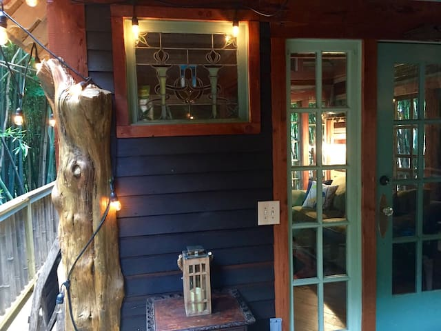 Front treehouse facade boasts late 1800s Victorian stained glass from Ohio and vintage sidelights and French door. The siding is reclaimed from an old Atlanta home
