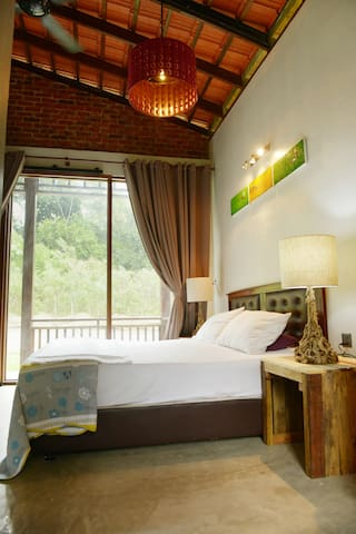 The main bedroom of our Family Villa with 1 king bed, 1 single bed, attached bathroom, air-conditioning and private terrace..