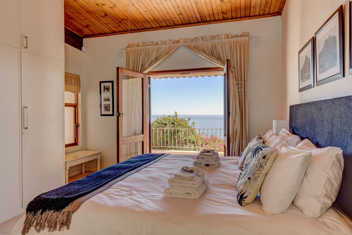 The spacious bedroom with a king size bed with doors leading onto the balcony overlooking the sea