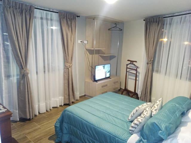 Habitación principal, cuenta con armario, tv Smart, excelente iluminación natural pues tiene dos ventanas, iluminación artificial inteligente con tres tonalidades de luz y una cama doble ideal para dos personas.