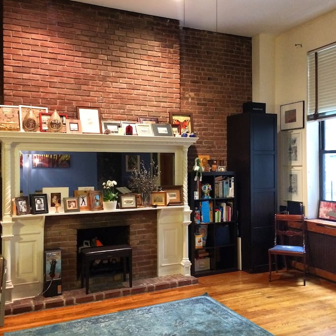 living room with queens sofa bed, mirror and 1910 brick wall with a fire place, small manhattan inner garden view:)