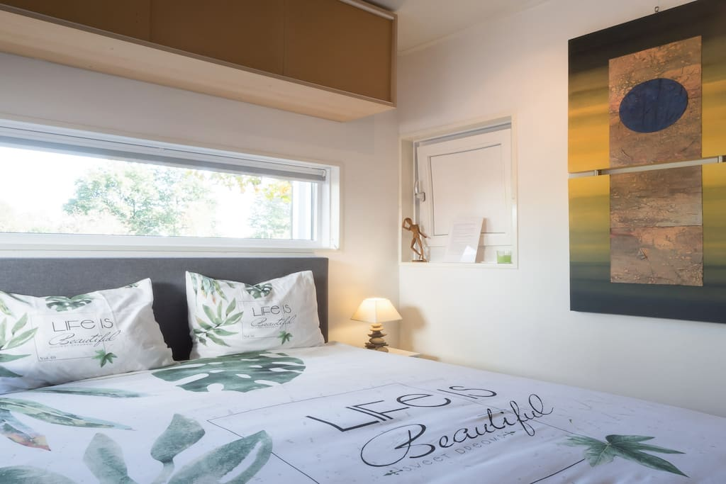 Warm and welcoming bedroom with tasteful  art details.