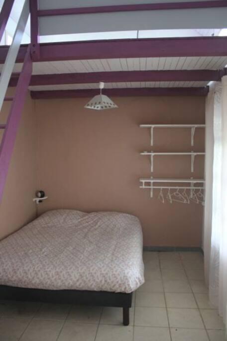 La chambre avec un vrai bon lit, des étagères et de quoi suspendre votre linge.  NB : Une grande moustiquaire a été ajoutée depuis la photo.