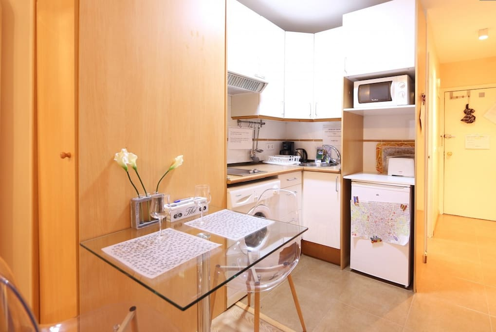 Kitchen with dinning table, washing machine, stove, microwave